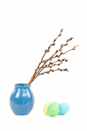 Willow catkins in blue vase with three dyed colored easter eggs isolated on white background, Happy Easter and spring concept with copy space