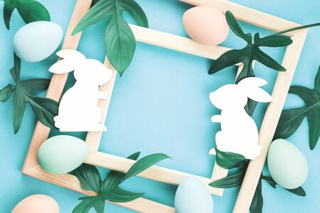 Happy Easter greeting card with pastel eggs and leaves in a frame, on trendy blue background with Easter bunnies. Close up with copy space