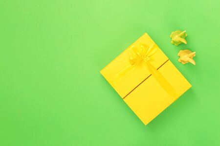 Yellow handmade bright gift box with a bow and two Easter bunnies on green background, flat lay with copy space. Happy Easter card concept