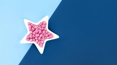 Shades of trending blue color with white star shaped bowl and pink sweets on monochrome background. flat lay with copy space. Color swatch mockup