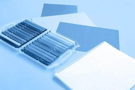 Trendy monochromatic white and blue color stationery, set of markers and notepad flat lay with copy space background. Minimalistic design for creative school or office concept