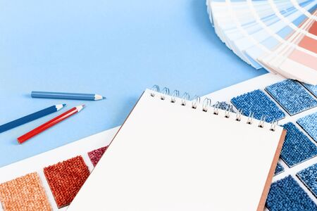 Shades of trending blue and red color swatches with a pencils and a notapad on blue background. copy space. Selective focus for interior or diy design nspiration. Color swatch mockup