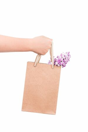 hand holding an eco buff paper bag with hyacinth flowers isolated on white. Spring or summer gift. Valentines, Womens, Mothers Day or gardening