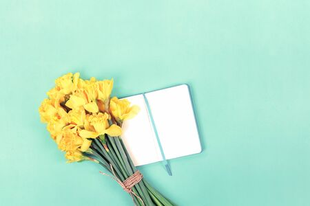 Daffodils bouquet with open notebook on mint green background. Flat lay with copy space, Valentines Womens or Mother Day celebration greeting card or bloggers mock up