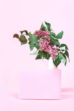 Lilac bouquet in a vase with pink envelope on feminine pink background. Love anniversary or valentines card with copy space