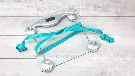 Green tape measure bow around glass weighing scale with slimming waste on a grey rustic surface. Healthy weight management resolutions and weight loss concept, sport fitness flat lay with copy space
