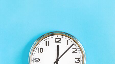Top of big plain wall clock on pastel blue background. Five past twelve oclock. Top view copy space, time management or school concept and summer or winter time change, opening hours, lunch break
