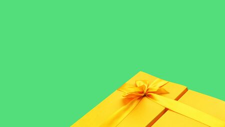 One glowing yellow gift box with ribbon and bow on brignt green table background. Top view. Minimal festive Easter gift or catching giveaway template. Copy space