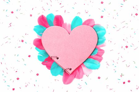 Creative love heart notepad with pink and mint feathers and scattered confetti and cake sprinkles isolated on white bavkground. St Valentines or Mothers Day, anniversary concept. Flat lay copy space. Banco de Imagens