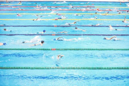 Indoor big sport swimming pool. Lots of children swimming along multiple lanes. Healthy active lifestyle concept. Sports school learning class or competition with copy space
