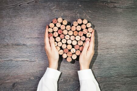 Two female hands holding a heart made of wine corks. Flat lay on wooden rustic background. 14 February. Passion, love and feelings St Valentines Day Card celebration concept with copy space Banco de Imagens