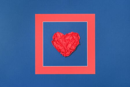 Framed creased red paper heart. Flat lay on dark blue background. 14 February. Passion, love and feelings St Valentines Day Card celebration concept with copy space Banco de Imagens