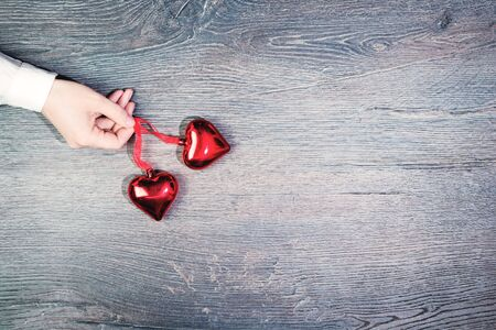 Female hand holding two red glass heart pendants. Flat lay on wooden rustic background. 14 February. Passion, love and feelings St Valentines Day Card celebration concept with copy space