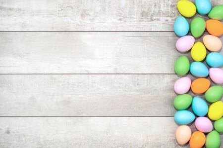 Several bright color dyed easter eggs on wooden background in flat lay with copy space. Border for Happy Easter minimal concept card or banner