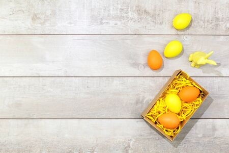 Several bright color dyed easter eggs with a rabbit on wooden background in flat lay with copy space. Border for Happy Easter minimal concept card or banner