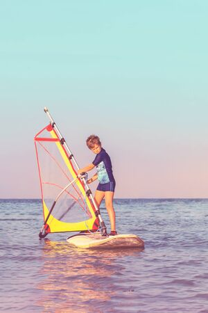 One caucasian child learning to windsurf at beautiful sunset light, close up. Calm sea waters. Winsurfing school. Travel and vacation leisure and sport with copy space