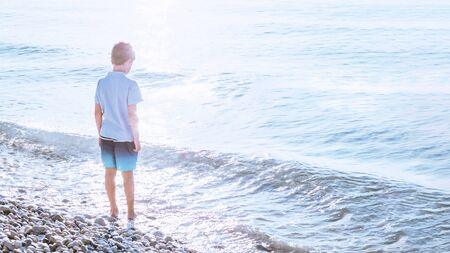 One child caucasian boy at the seaside pebble beach with glowing sparling water and light flares. Tender blue sunrise waters. Exotic travel and destination scenic vacation with copy space banner