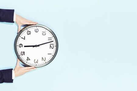 Hands of woman in business suit hold big plain wall clock on trendy pastel blue background. six oclock. Close up with copy space, time management concept and opening or closing time, schedule Banco de Imagens