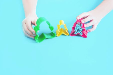 Happy family concept cut outs in hands of a child. Mother, father, son, daughter and pregnancy top view with copy space