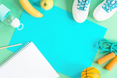 Sport items and color paper, scissors, pencils notebook and various school stationery and fruit apple banana on blue background. Flat lay with copy space for back to school education and craft concept