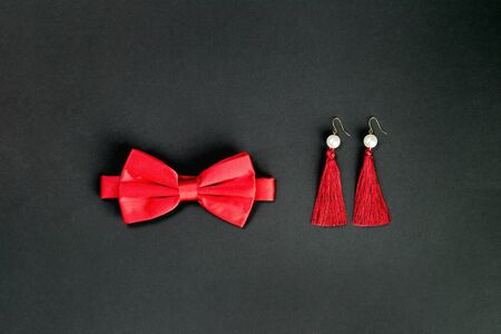 red bow tie and fancy earings. Flat lay on black background. 14 February. Passion, love and feelings St Valentines Day Card celebration concept with copy space