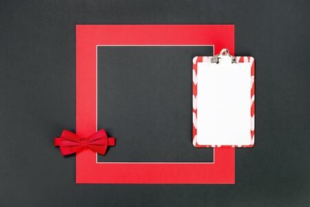 Framed red bow tie and message note pad. Flat lay on black background. 14 February. Passion, love and feelings St Valentines Day Card celebration concept with copy space Banco de Imagens