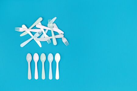 Scattered white reusable eco plastic cutlery on aqua blue color background. Eco environment friendly zero waste party concept flat lay with copy space. Informed choice