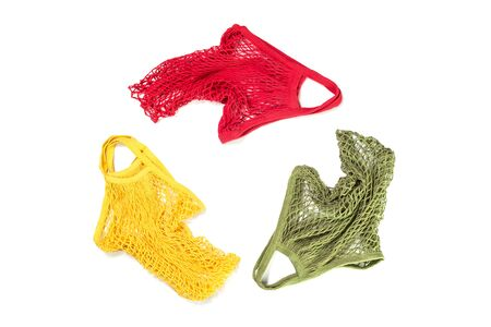 Bright crochet net or mesh eco shopping bags form recycling symbol isolated, creative flat lay for environment friendly zero waste and palstic free ecological lifestyle creative concept. Copy space Banco de Imagens