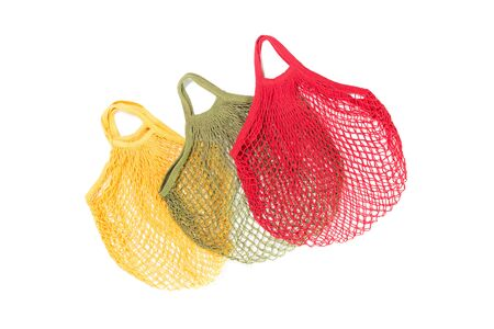 Three bright crochet net or mesh eco shopping bags isolated, creative flat lay for environment friendly zero waste and palstic free ecological lifestyle concept. Copy space Banco de Imagens