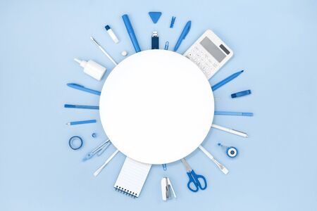 Assorted office and school blue stationery on pastel monochrome background . Flat lay border frame with white round copy space for back to school or education and craft concept Banco de Imagens