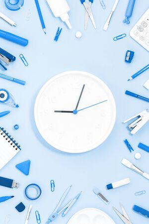 Assorted office and school blue stationery on pastel monochrome background with white clock 9 oclock. Flat lay with copy space for back to school or education and craft or arts concept