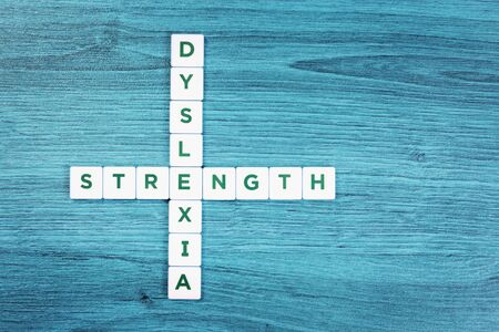 Dyslexia and strength word cubes on blue wooden desk background, reading difficulty awareness and disorder concept. Education and neurology with copy space