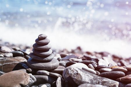 Stone pebble tower balancing on the beach with sparkling sea waters spash bokeh. Copy space. Balance and mindfulness. Zdjęcie Seryjne