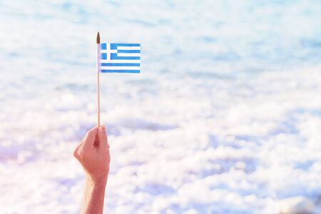 Hand holding Greek waving flag flying over sea water waves. Travel to Greece or national Day. Copy space Imagens