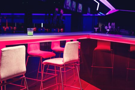 Glass of bright green neon cocktail on a bar table in night club blue and red lights. Party or nightlife entertainment with copy space