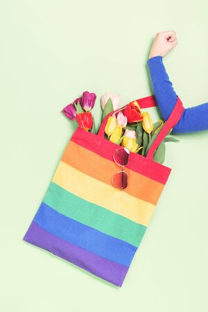 Female hand clenched fist holding a LGBTQ pride rainbow flag canvas tote bag with tulip flowers and heart shaped sunglasses. top view. Homophobia, Transgender or lesbian visibility day and awareness
