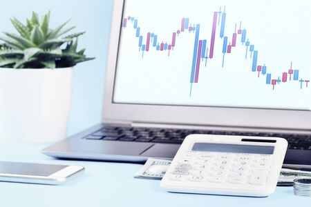 Finance stock chart on laptop with calculator and money notes and coins on blue. Finance markets investments loans earnings concept. Personal accounting debts and credits bankruptcy with copy space Reklamní fotografie