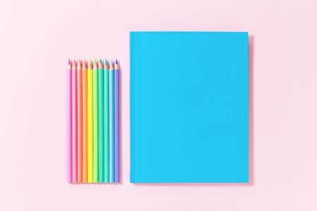Set of colored pastel pencils and blue plain mockup notebook on pink. Bright tender multicolored back to school concept flat lay with copy space, education or office stationery for designers 免版税图像