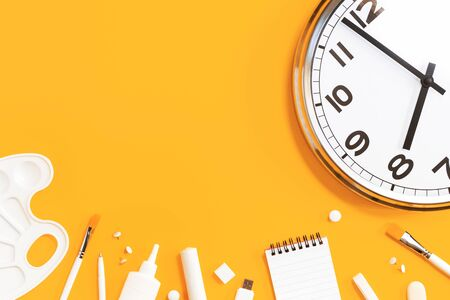 Part of analogue plain wall clock on trendy yellow background with white stationery items. Eight o'clock. Close up with copy space, time management or school concept and opening hours time