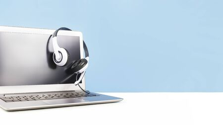 Laptop with blank screen with headphones on white desk blue background and copy space. Distant learning or working from home, online courses or shopping minimal concept. Helpdesk or call center