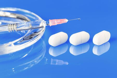 one glass syringe with a drop and white pills on glass plate with copy space close up view. Medication safe consumption and treatment, vaccine and immunization. Health and pharmacy concept