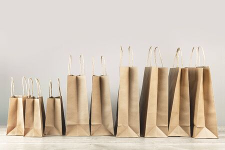 Assorted craft buff paper carry bags in a row on grey wood. Delivery service courier of goods and grocery, shopping or sale. Environment and eco friendly packaging, plastic free takeaway packing Standard-Bild