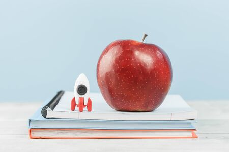 Organized office or school desk. Toy rocket and big red apple on pile of notebooks on wooden desk. Copy space for back to school or education knowledge craft and innovative startup concept