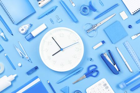 Assorted office and school white blue stationery on blue background. White clock in the middle. Flat lay copy space. back to school or education and craft concept. monochrome banner. Time management