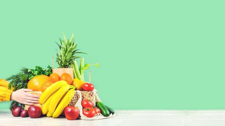 Delivery of grocery. Hands hold chest with fresh fruit and vegetables bright green. Eco friendly responsible lifestyle and shopping. Healthy eating, zero waste concept. Copy space banner. Donation.