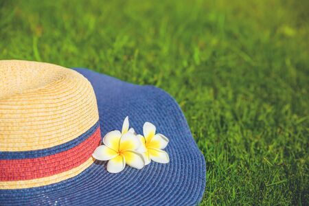 Summer feminine straw hat with plumeria flowers on green grass. Summer spring and exotic vacation concept with copy space