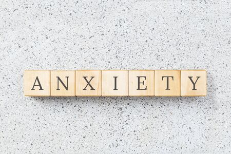 Anxiety word made with wooden buildning blocks on grey cork background. Uncertainty and panic concept. Minimal