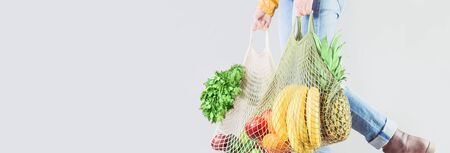 Delivery of grocery. Unrecognizable girl holds two mesh shopper bags with fruit and vegetables. Eco friendly responsible lifestyle and shopping. Healthy eating, zero waste concept. Copy space banner