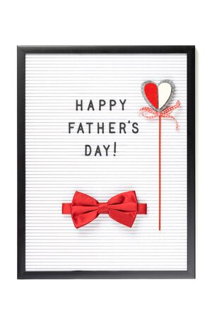 Happy Father's Day text on letter board with red bow tie and a heart. isolated on white. Minimal framed text poster or banner. Copy space. Sale mockup Imagens