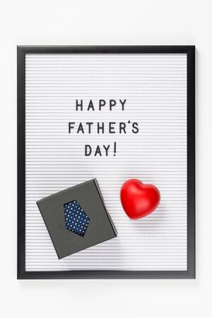 Happy Father's Day text on letter board with boxed dark blue tie isolated on white. Minimal framed text. Father's Day sale mockup template. Copy space